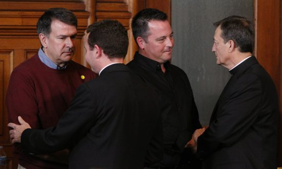 From left, Al Michaud, Bishop Andrew Cozzens, Jim Keenan and Father Charles Lachowitzer exchange handshakes and greetings during the press conference. Michaud and Keenan are clergy abuse survivors. Dave Hrbacek/The Catholic Spirit