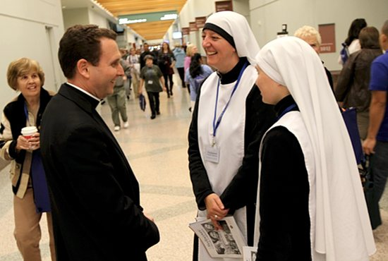 Bishop Andrew Cozzens talks with members of the Handmaids of the Heart of Jesus, including Mother Mary Clare, center, at the Rediscover: Catholic Celebration Oct. 4 at the Minneapolis Convention Center. Bishop Cozzens helped start the order, which is in the Diocese of New Ulm. Dave Hrbacek/The Catholic Spirit