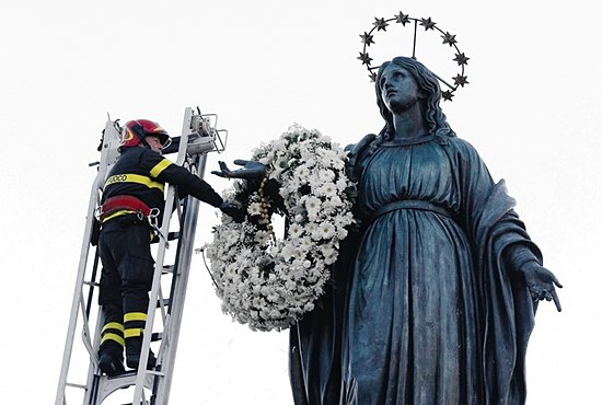 FEAST DAY TRADITION A firefighter places a wreath on a statue of Mary overlooking the Spanish Steps in Rome Dec. 8, the feast of the Immaculate Conception. Rome's firefighters have observed the tradition every year since 1857. CNS/Paul Haring