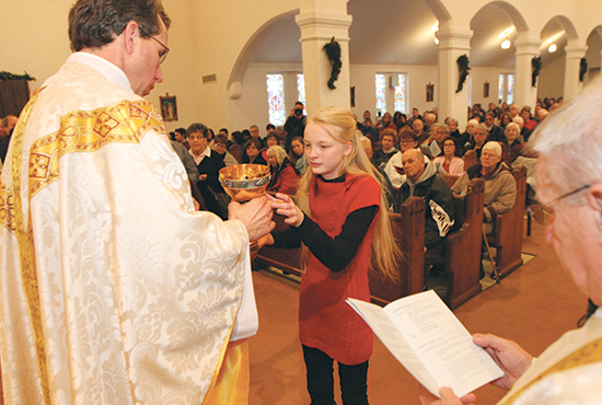 Father Donald DeGrood, pastor of Blessed Sacrament in St. Paul, passes a chalice to Amanda Showalter during the final Mass Jan. 11 at the Blessed Sacrament LaCrosse Avenue site. Showalter and other parishioners received sacred items from the church and took them to the Stillwater Avenue site, where they were placed in front of the altar. The Mass ended with Father DeGrood closing the doors and offering a final prayer.  Dave Hrbacek/The Catholic Spirit
