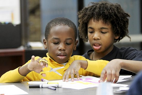 Elijah Short, right, a sixth-grader at St. Stephen School in Anoka, helps his kindergarten buddy Ajim Tubuo work on an art project for religion class as part of the school's Disciples and Friends program. Dave Hrbacek/ The Catholic Spirit