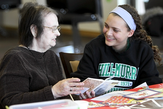 Sierra Arradondo, right, a ninth-grader at Hill-Murray School in Maplewood, helps Anne Fearing, a resident at Thomas T. Feeney Manor in Minneapolis, put together a memory book Feb. 26. Arradondo came with other classmates to work with residents. Dave Hrbacek/The Catholic Spirit