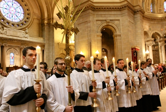 Altar servers hold candles and a processional cross decorated with a palm as they wait for the Palm Sunday Mass processional at the Cathedral of St. Paul March 29. Dave Hrbacek / The Catholic Spirit