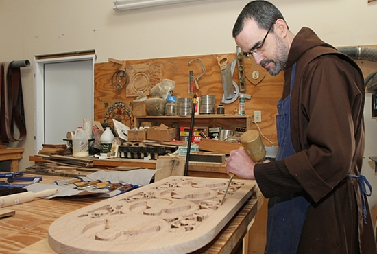 Carmelite Brother Joseph Bubanko uses hand tools to work on a carving that will be displayed in the order's monastery in Lake Elmo. The wood he uses comes from trees harvested on the grounds. Dave Hrbacek/The Catholic Spirit