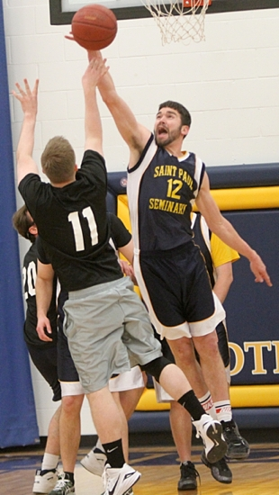 Basketball 2: Seminarian Doug Liebsch blocks a shot by Father Michael Barsness during action in the championship game.