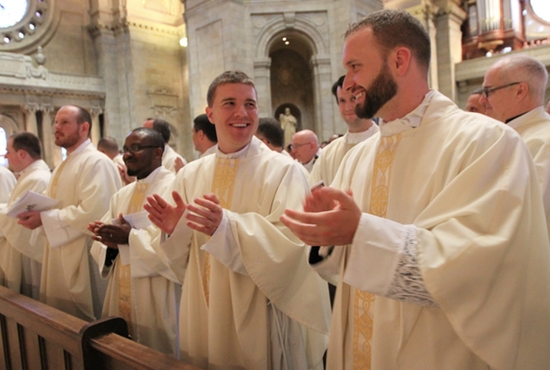 Newly ordained Fathers Peter Hughes, right, and James Stiles break out in smiles at the end of their ordination Mass May 30 at the Cathedral of St. Paul. Joining them in the front pew are Fathers John Powers, left, Thomas McKenzie and Bruno Nwachukwu. Others who were ordained that day are Fathers Jake Anderson, Byron Hagan and Alvaro Silva. Dave Hrbacek/The Catholic Spirit