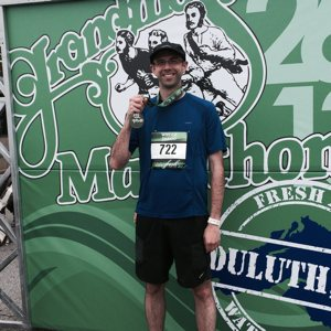 Father Nate LaLiberte shows off his race medal after successfully running 26.2 miles.