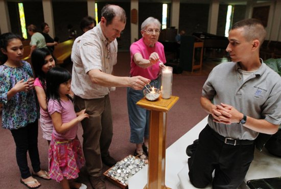 David McSherry, center, lights a candle at St. Joseph in West St. Paul with three of his children: Isabella, left, Teresa and Francesca. At right is Cord Dorcey. All are parishioners of St. Joseph. Dave Hrbacek/The Catholic Spirit