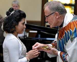 Father Steve LaCanne, pastor of  St. Leonard of Port Maurice in Minneapolis, distributes the Eucharist during first Communion May 3.  Jim Bovin/For the  Catholic Spirit