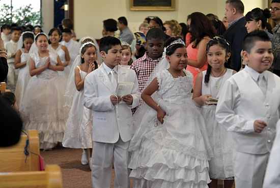 Children enter the church of St. Leonard of Port Maurice in Minneapolis May 3 to receive first Communion. Jim Bovin/For The Catholic Spirit