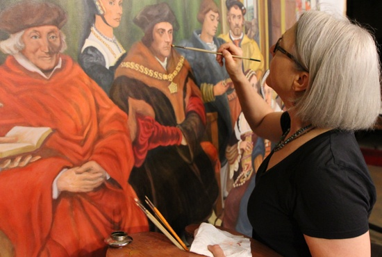 Artist Mary Klein, a parishioner of St. Thomas More in St. Paul, works on the painting