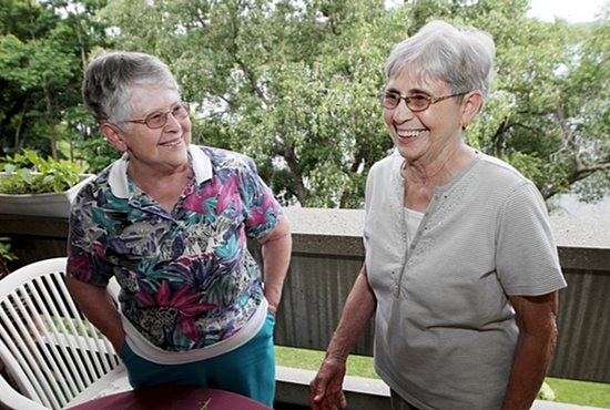 Sister Phyllis (left) and Sister Shirley reminisce about their vocation on the balcony of the St. Paul apartment they share. Dave Hrbacek/The Catholic Spirit