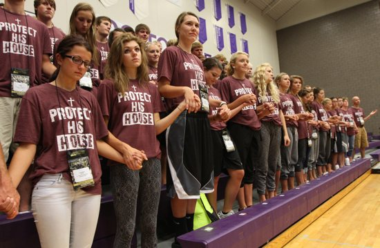 From left, Katie Horner, Kate Long and Shaina Weigel of St. Philip Neri in Napoleon, North Dakota, pray during Mass July 24 at the Steubenville North conference at the University of St. Thomas. Dave Hrbacek/The Catholic Spirit