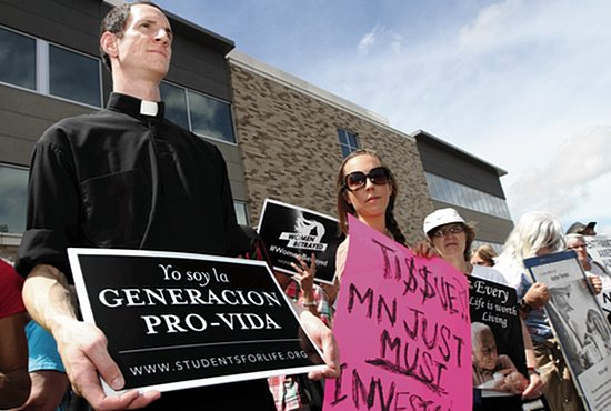 "Father Nick VanDenBroeke, left, of Divine Mercy in Faribault holds a sign reading ""I am the pro-life generation"" in Spanish at a pro-life rally July 28 at Planned Parenthood in St. Paul. Dave Hrbacek/The Catholic Spirit"