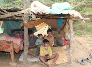 Subu Pariyar and his children sit inside a makeshift shelter May 9 on top of Baretol mountain in Nepal. Their home was destroyed in the magnitude-7.3 earthquake April 25. CNS/Anto Akkara