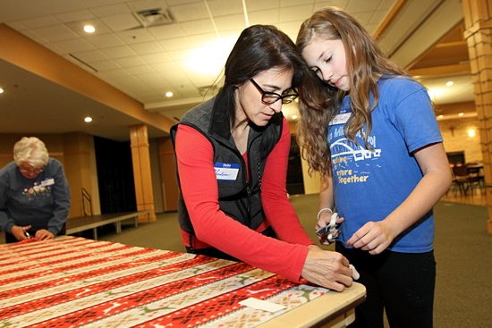 Christina Gapp, left, and her daughter Amy work to finish a blanket corner. Dave Hrbacek/The Catholic Spirit