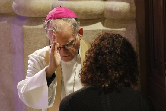 Auxiliary Bishop Peter J. Byrne of New York blesses a woman after hearing her confession Dec. 9 at St. Patrick's Cathedral in New York City. The Archdiocese of St. Paul and Minneapolis will hold 24 hours of confessions March 4-5 at the Cathedral of St. Paul and Basilica of St. Mary. CNS