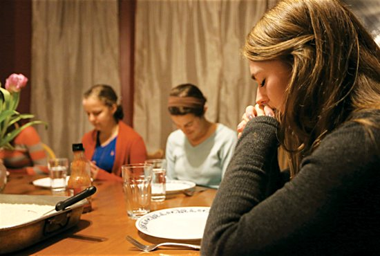 Kayla Lynch, right, joins in prayer before dinner along with other members of an SPO women's household near the University of Minnesota. Joining her are Ariel Garsow, left, and Alex Bosch. Dave Hrbacek/ The Catholic Spirit