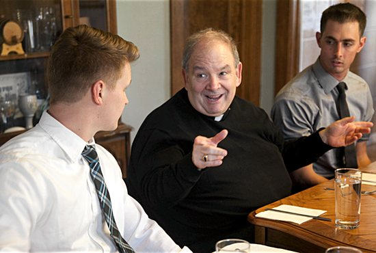 Archbishop Hebda talks with Peter DeMarais, left, and Jimmy Abbot, right, during dinner at a St. Paul's Outreach house in St. Paul April 19. Courtesy Meg Miller, St. Paul's Outreach