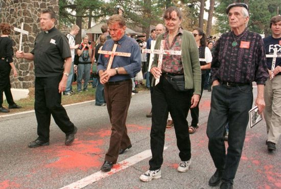 Jesuit Father Daniel Berrigan, right, and actor Martin Sheen, third from right, join the annual School of the Americas protest in 1999 at Fort Benning, Ga. Father Berrigan, an early critic of U.S. military intervention in Vietnam who for years challenged the country's reliance on military might, died April 30 at 94. CNS photo/Quirin, The Messenger)