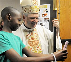 Archbishop Bernard Hebda takes a selfie with 11-year-old Hubert Nyombi after the 50th anniversary Mass at St. Rita in Cottage Grove April 17. Dianne Towalski/ For The Catholic Spirit