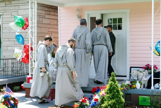 Franciscan Friars of the Renewal from New York pay their respects at the childhood home of boxing legend Muhammad Ali June 5 in Louisville, Ky. Ali died June 3 at age 74 after a long battle with Parkinson's disease. CNS photo/John Sommers II, Reuters)