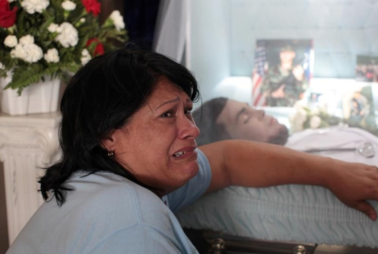 Lucyvette Padro mourns next to the body of her son, Angel Candelario Padro, during his wake June 17 in his hometown of Guanica, Puerto Rico. Candelario was of the victims of the June 12 mass shooting at the Pulse nightclub in Orlando, Fla. CNS photo/Alvin Baez, Reuters