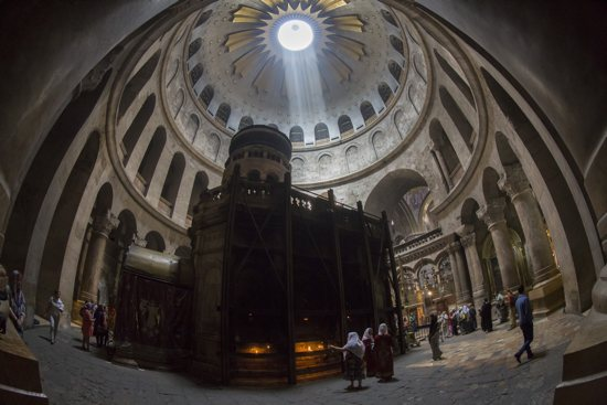 Tourists and Christian pilgrims visit the tomb where it is believed Christ was buried inside the Church of the Holy Sepulcher in Jerusalem April 17. For the first time in 200 years, experts have begun a restoration of the Edicule of the Tomb. CNS/Jim Hollander, EPA