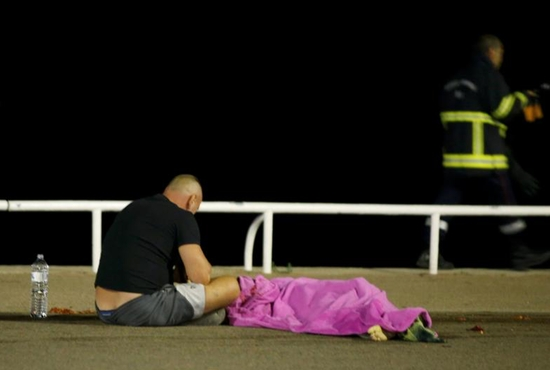 A man sits next to a body on the ground July 15 after at least 84 people were killed in Nice, France, when a truck ran into a crowd celebrating the Bastille Day national holiday July 14. CNS photoEric Gaillard, Reuters