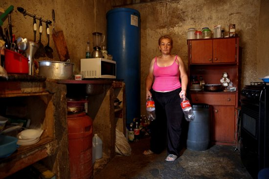 Yunni Perez holds plastic bottles used to carry water while she poses for a photo April 3 inside her home in a slum area of Caracas, Venezuela. CNS/Carlos Garcia Rawlins, EPA