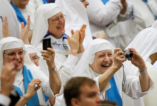 Nuns clap and take pictures as Pope Francis arrives to lead his general audience in Paul VI hall at the Vatican Aug. 10. CNS photo/Max Rossi, Reuters