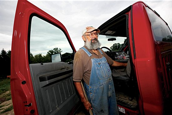 Deacon Kittok stands outside of his Ford F-450 pickup truck as he unloads dirt excavated from a nearby cemetery. Dave Hrbacek/The Catholic Spirit