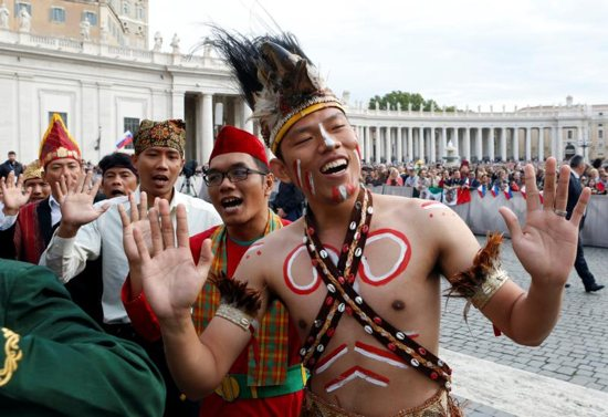Pilgrims from Indonesia wave before Pope Francis arrives to lead his weekly audience Sept. 21 in St. Peter's Square at the Vatican. CNS photo/Remo Casilli, Reuters