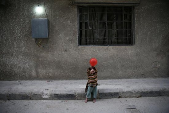 """A child plays with a balloon in Douma, Syria Nov. 13. Pope Francis has called events unfolding in the war-torn country a veritable """"workshop of cruelty."""" CNS photo/Bassam Khabieh, Reuters"""