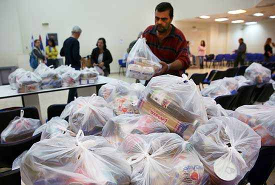 Bags of food and supplies are distributed to poor people in Athens, Greece, Nov. 9. CNS/Orestis Panagiotou, EPA