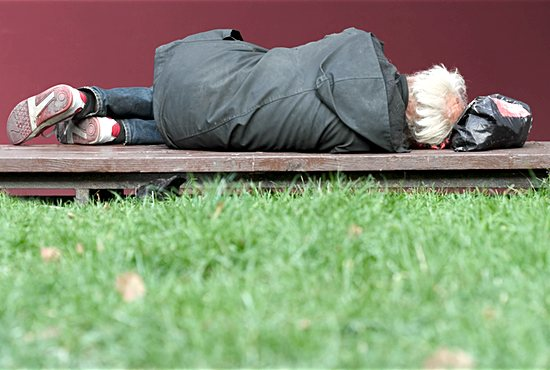 Homeless man sleeping on a bench outside
