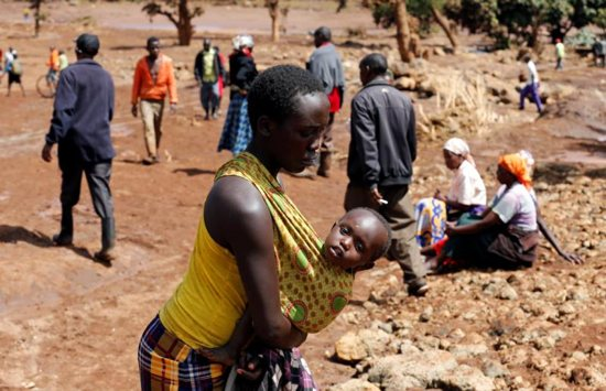 A woman carries her child near destroyed houses in Solai, Kenya