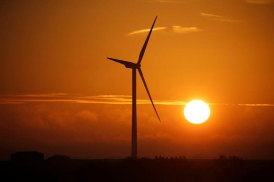 A power-generating windmill is pictured during sunrise in Escarmain, France