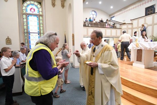Baltimore Archbishop William Lori gives Communion to Kevin Marron, a Baltimore Gas and Electric employee