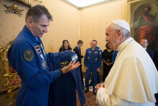 Pope Francis accepts a gift of a flight suit from Italian astronaut Paolo A. Nespoli