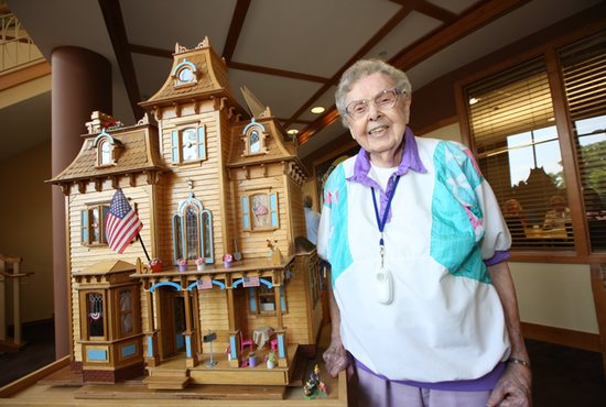 Sister of St. Joseph Marguerite Turgeon, 101, stands June 6 next to a miniature Victorian house she assembled that is on display at Carondelet Village in St. Paul where she lived.