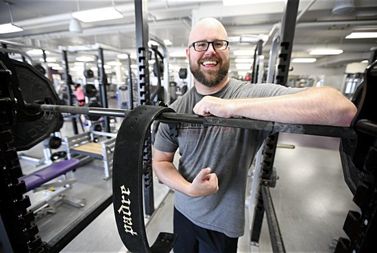 Father John Floeder, dean of seminarians at the St. Paul Seminary School of Divinity, smiles during a break in his weight- lifting routine
