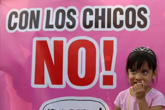 "A child stands next to a sign reading ""With the Children, No!"" during a protest in early February against child abuse and violence in Lima, Peru."