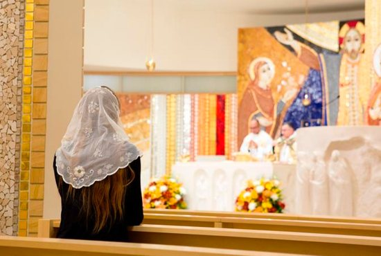 A woman prays during Mass at the St. John Paul II National Shrine in Washington