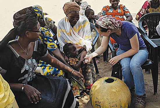 Bridget Gerenz in a meeting with women from a village near Diouroup in Senegal's Fatick region to discuss thresher performance and their desired improvements.