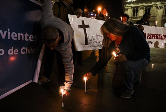 People place candles in front of the Metropolitan Cathedral of Santiago Aug. 20 during a demonstration against sexual abuse committed in the Chilean Catholic Church.
