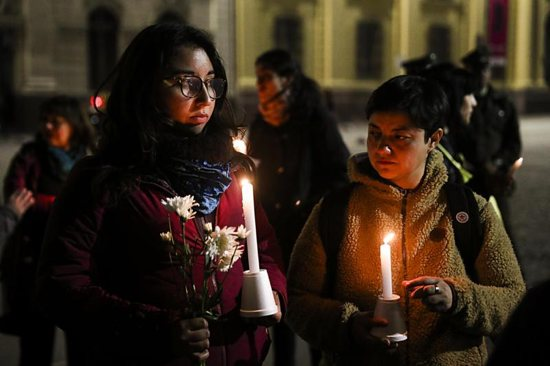 Demonstrators hold candles and flowers Aug. 20 in front of the Metropolitan Cathedral of Santiago, Chile.