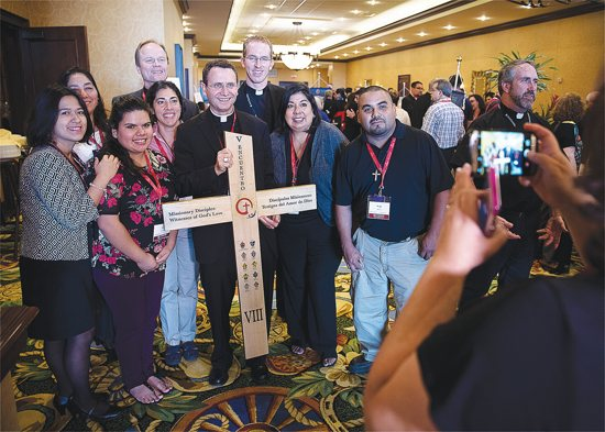 Auxiliary Bishop Andrew Cozzens poses for a photo Sept. 20 with delegates prior to the start of the Fifth Encuentro in Grapevine, Texas.
