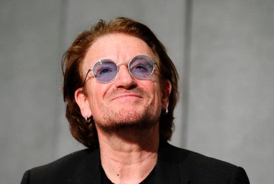Bono, the lead singer of U2, smiles during a news conference in the Vatican press hall after meeting Pope Francis at the Vatican Sept. 19.