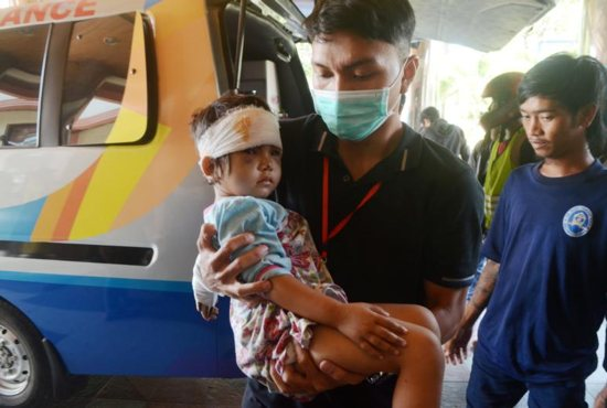 A man carries an injured child Oct. 2 in Makassar, Indonesia after an earthquake and tsunami.